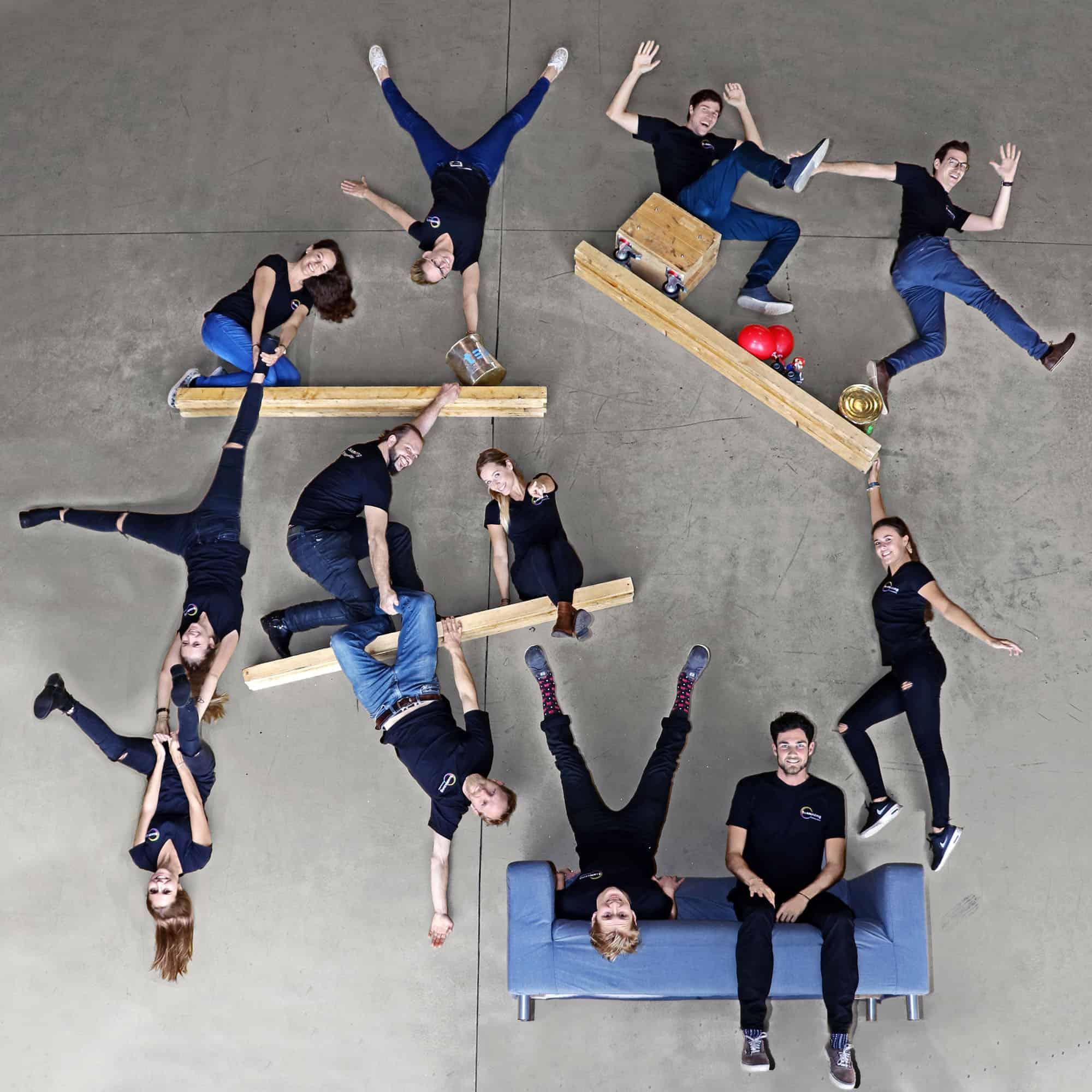 Ein Gravity Shot. Menschen liegen am Boden und tun so als würden sie sitzen und stehen.