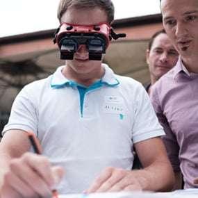 Mann hat eine Umkehrbrille auf und versucht damit unter Anweisung eines Teamkollegens etwas zu zeichnen